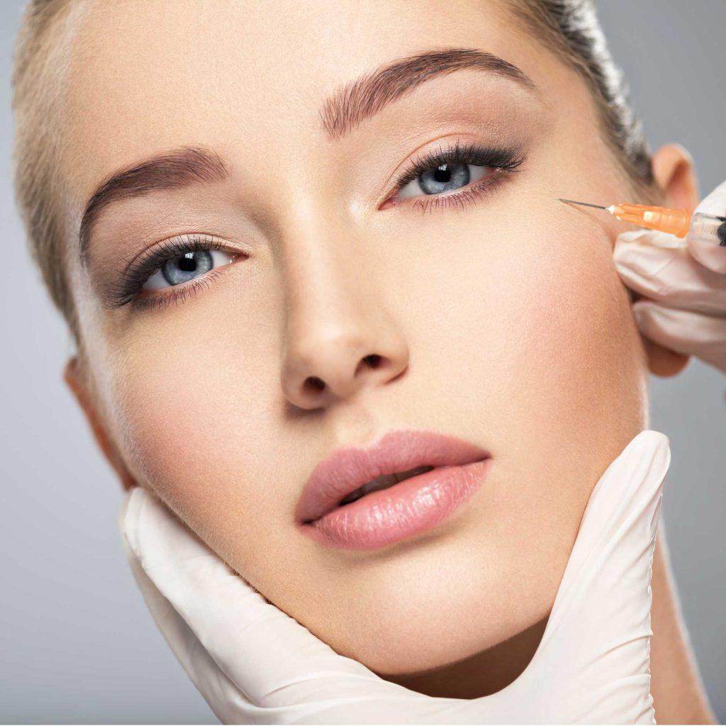 Botolinum - Frau bekommt Injektion mit Botox in die Wange